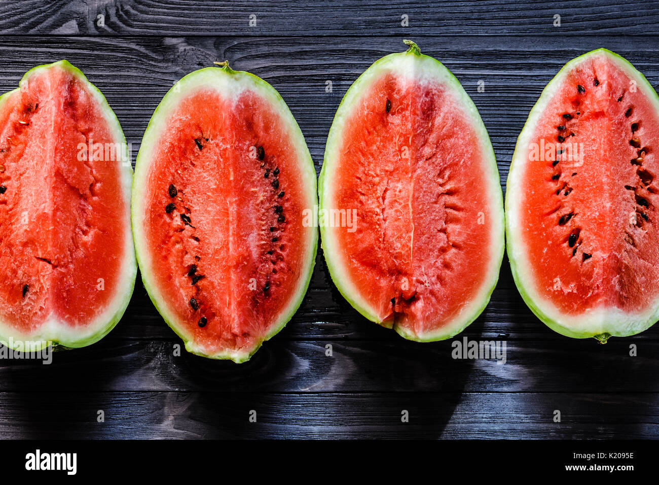 Background of fresh ripe watermelon slices on black wooden table. Top view. - Stock Image