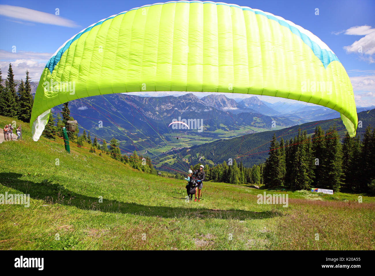 Paragliders starting a tandem jump, Planai, Schladming, Styria, Austria - Stock Image