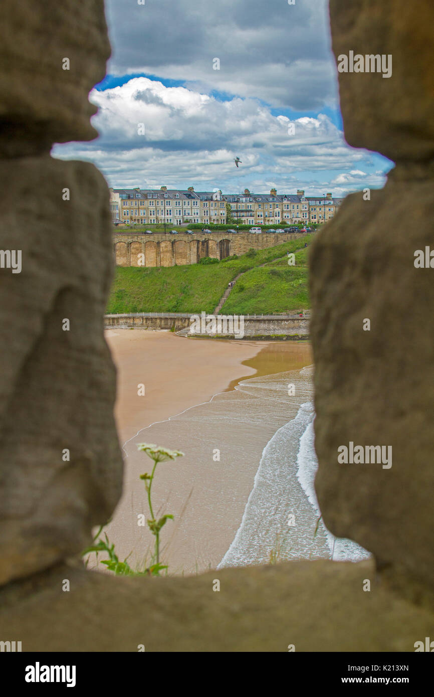Town of Tynemouth and adjacent sandy beach under blue sky viewed through window in ruins of historic castle, England - Stock Image