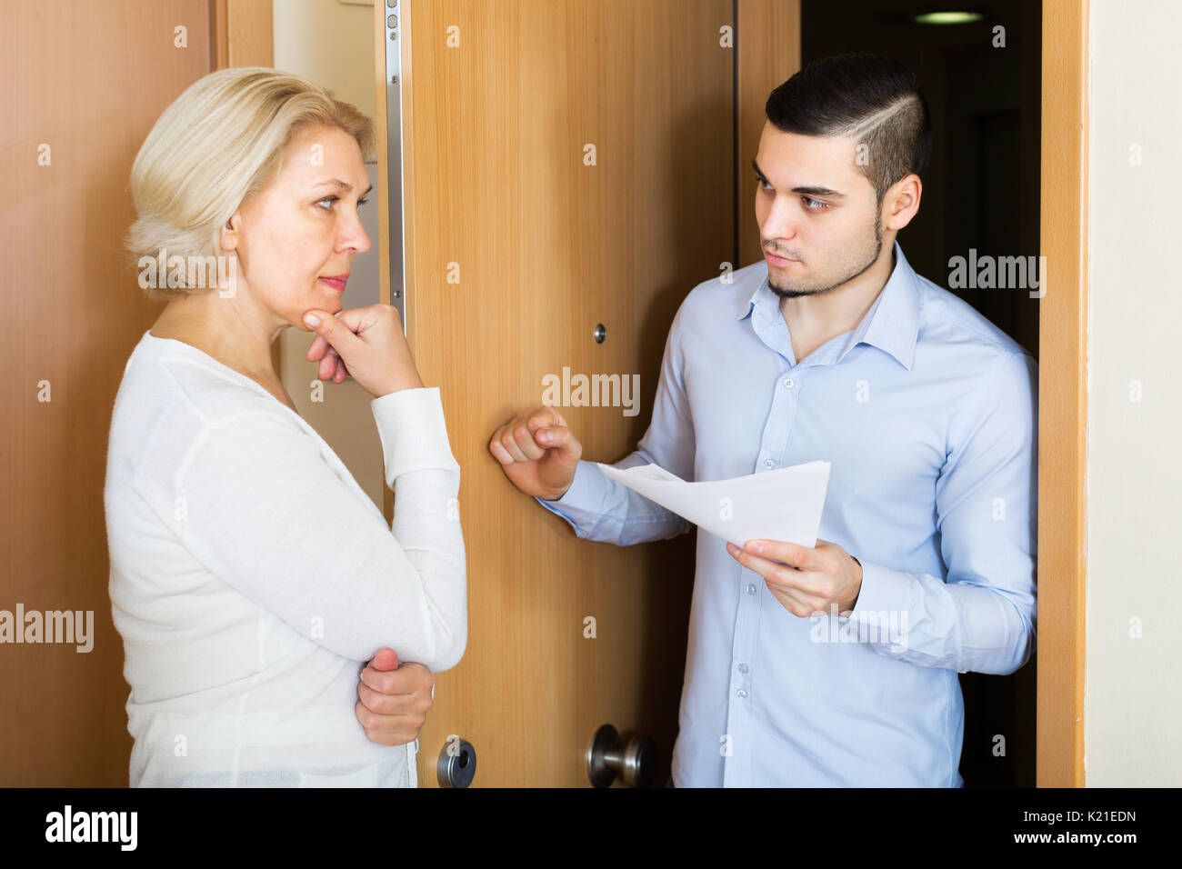 Young collector is trying to get the arrears from woman at home door - Stock Image