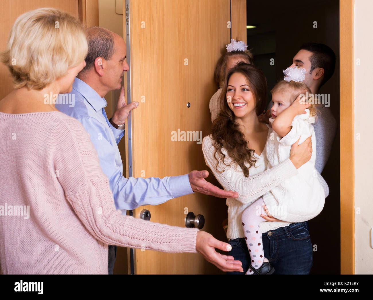 smiling young family with two daughters visiting grand parents - Stock Image