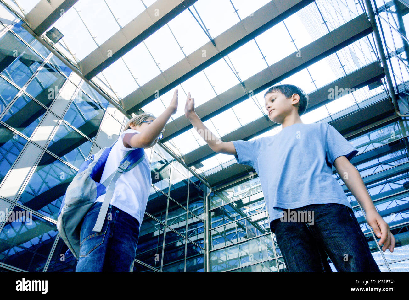 Two boys giving each other a high five outdoors - Stock Image