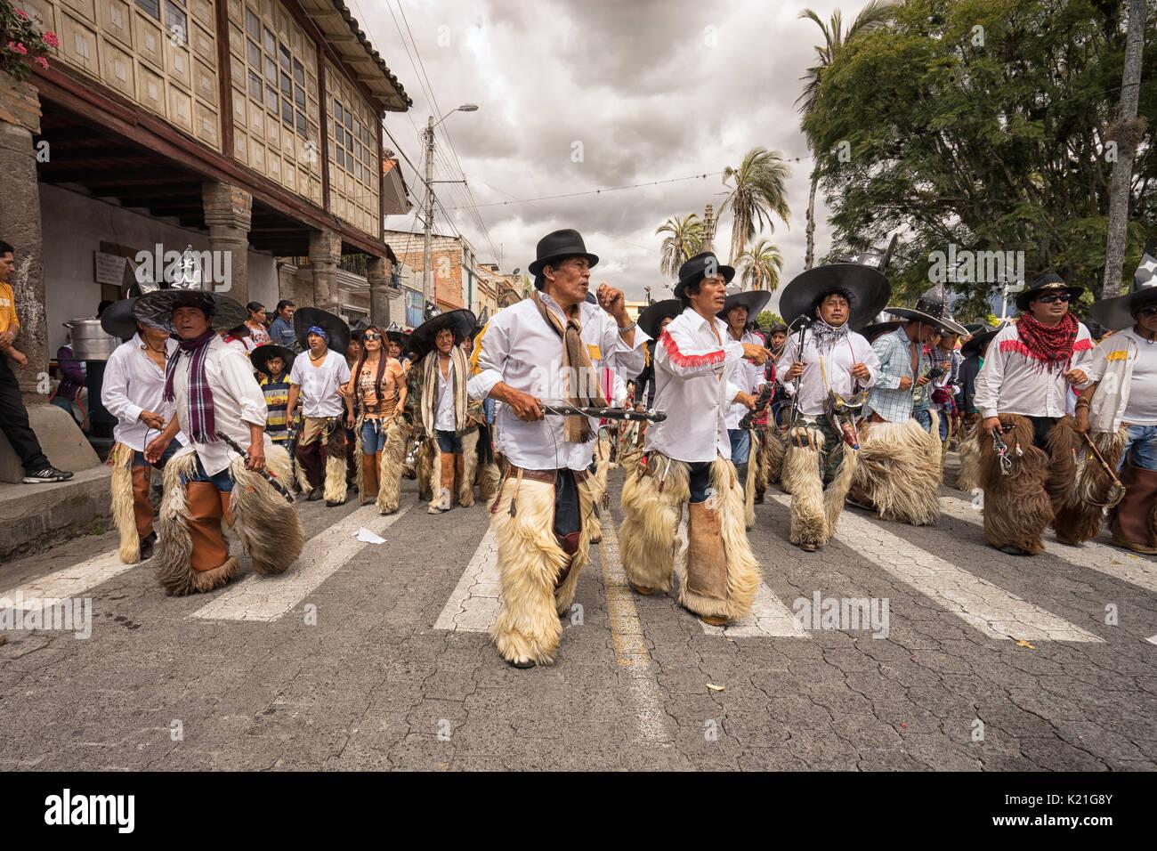 June 24, 2017 Cotacachi, Ecuador:  indigenous kichwa men wearing chaps dancing at the Inti Raymi parade at summer solstice - Stock Image