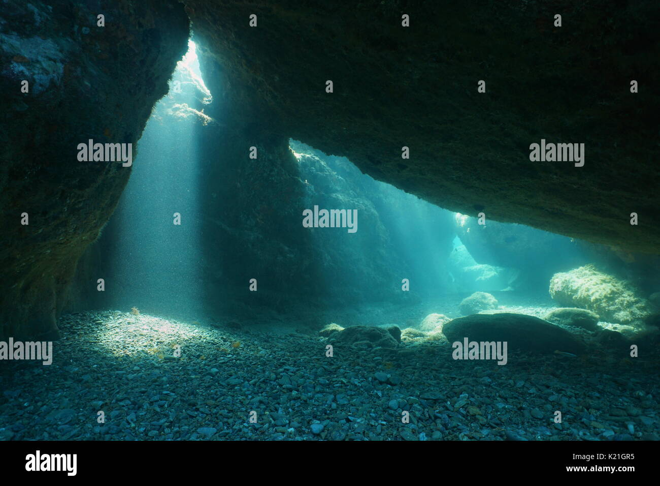 Below big rocks underwater with sunbeam from hole, Mediterranean sea, natural scene, Pyrenees Orientales, Roussillon, France - Stock Image
