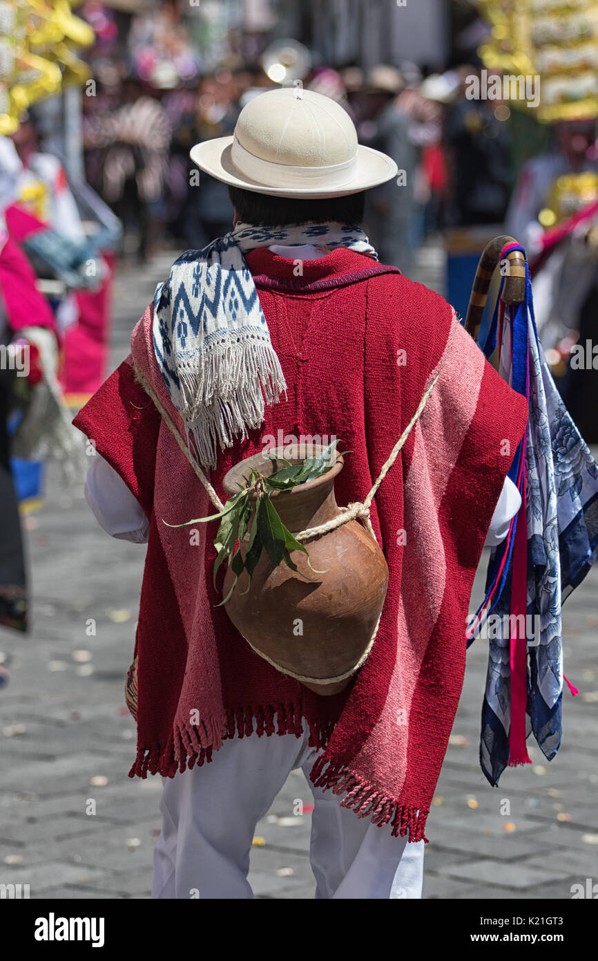 June 17, 2017 Pujili, Ecuador: man in traditional wear carrying a clay vase on his back on rope at the Corpus Christi parade - Stock Image