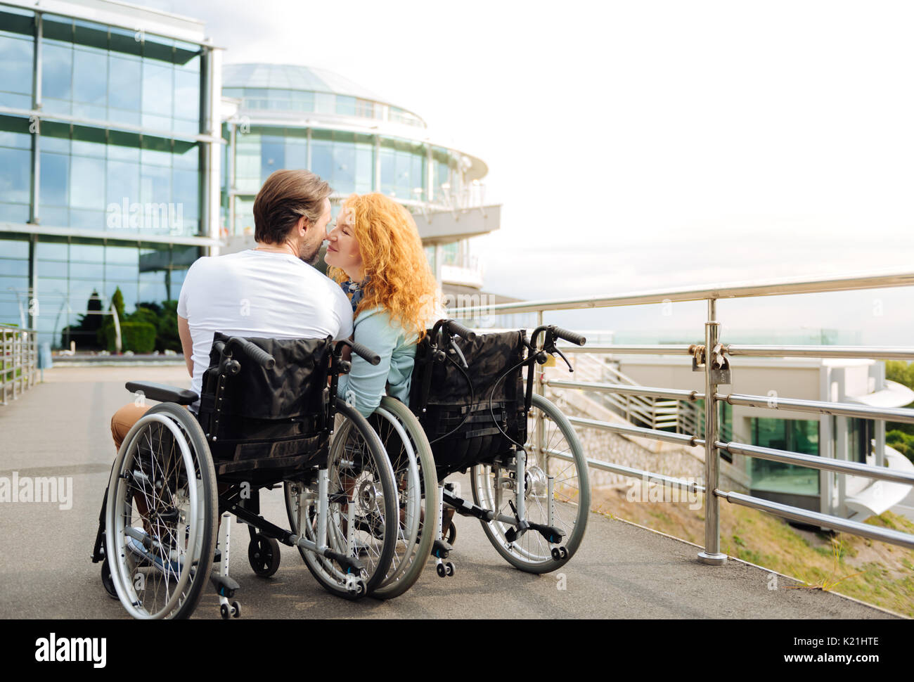 Rear view of a senior wheelchaired couple kissing - Stock Image