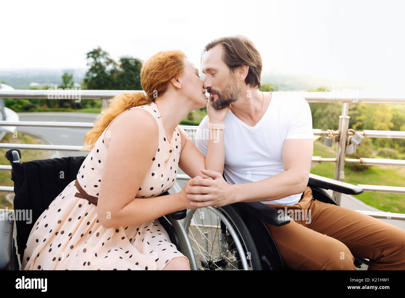 Nice wheelchaired couple kissing outdoors - Stock Image