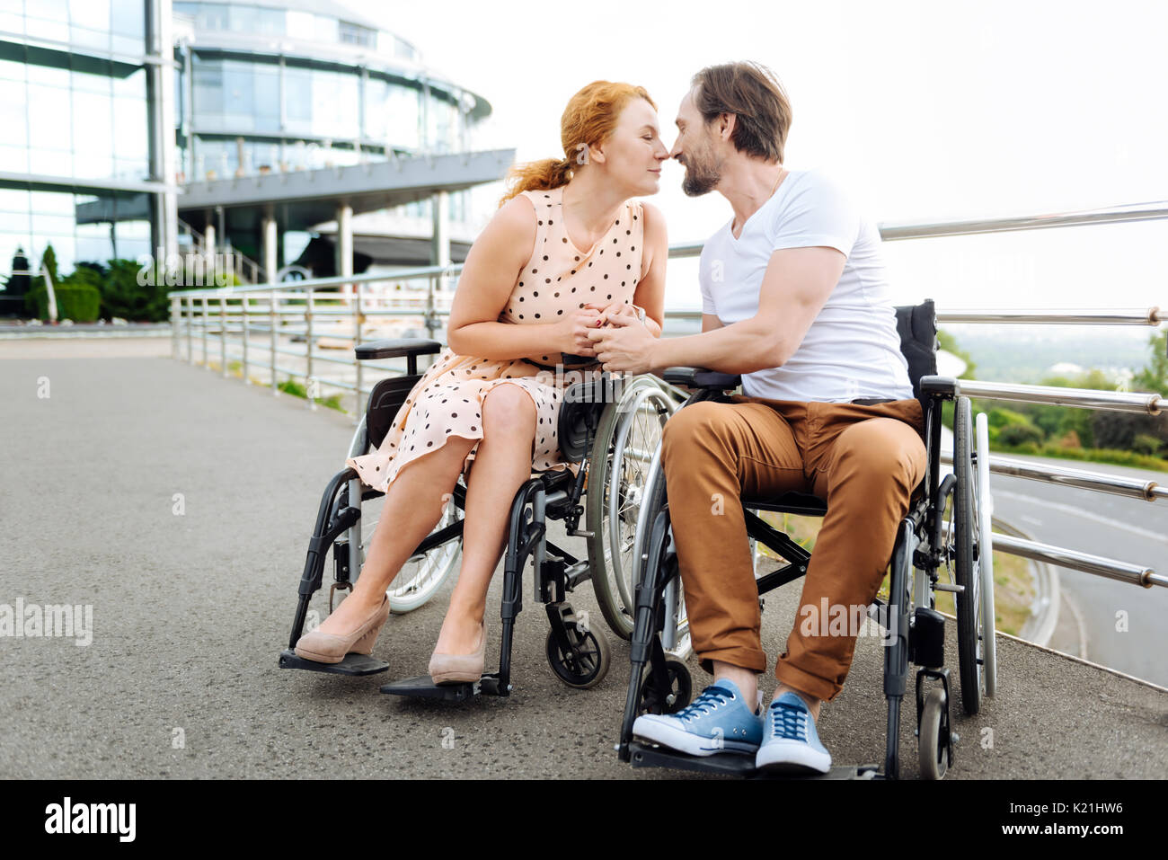Pleasant disabled senior couple kissing outdoors - Stock Image