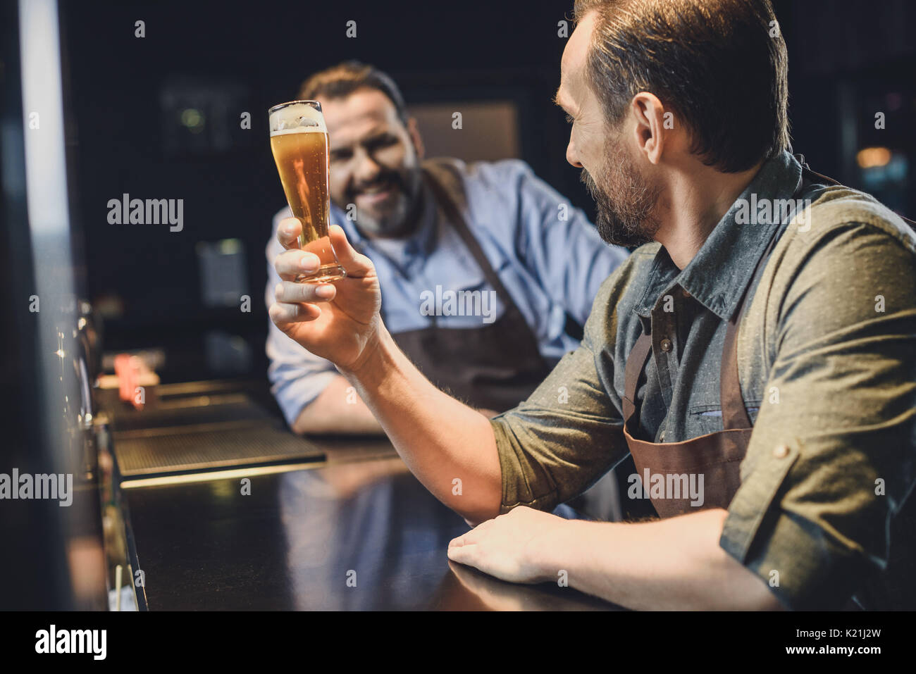 Male brewery worker holding small glass of beer - Stock Image