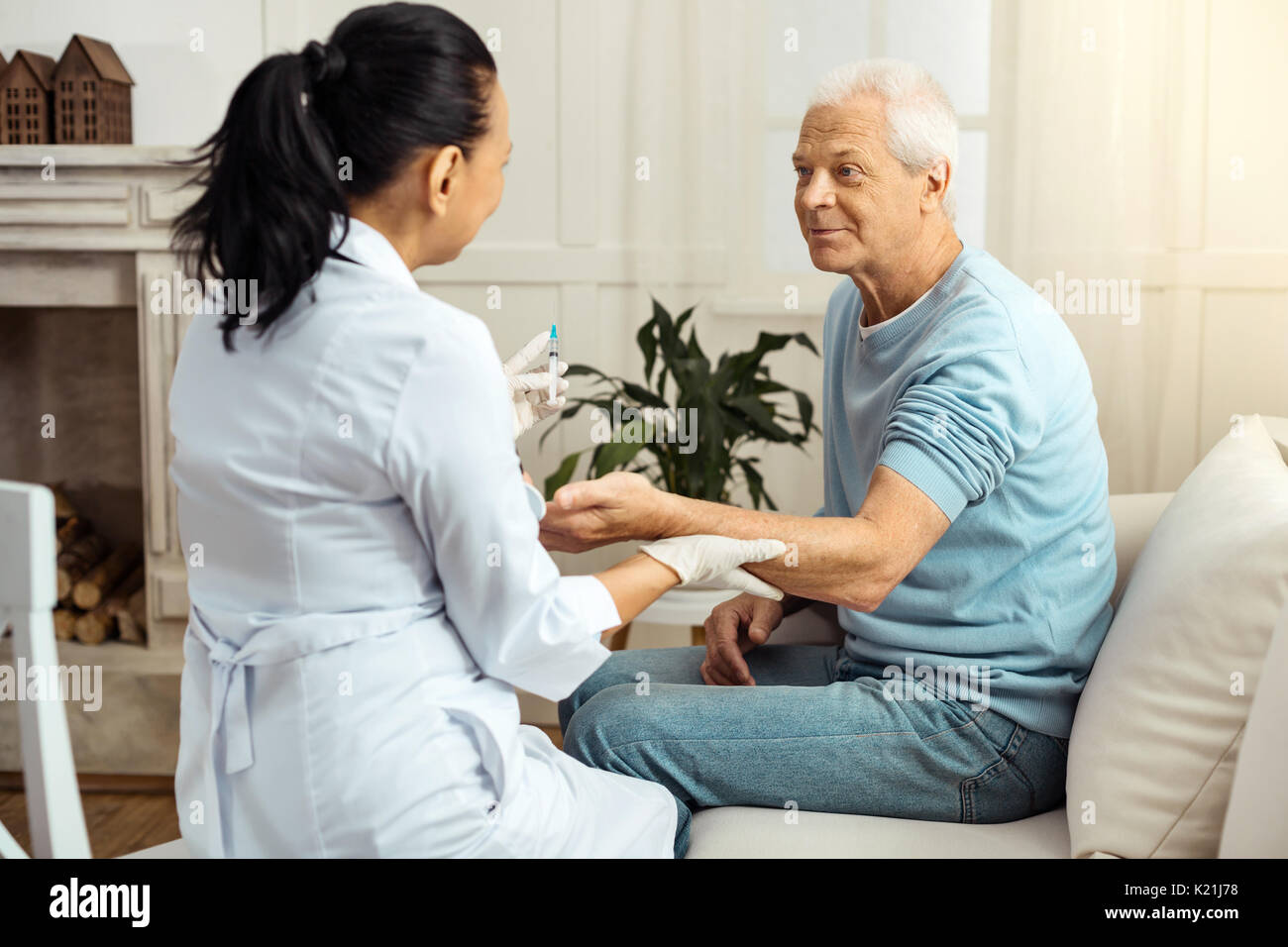 Pleasant nice nurse holding her patients hand - Stock Image