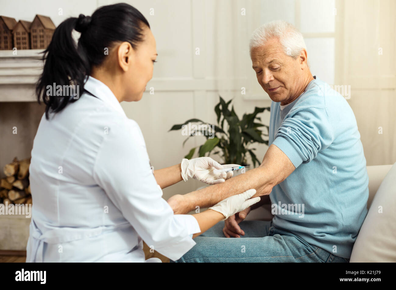 Skillful medical worker doing an injection - Stock Image