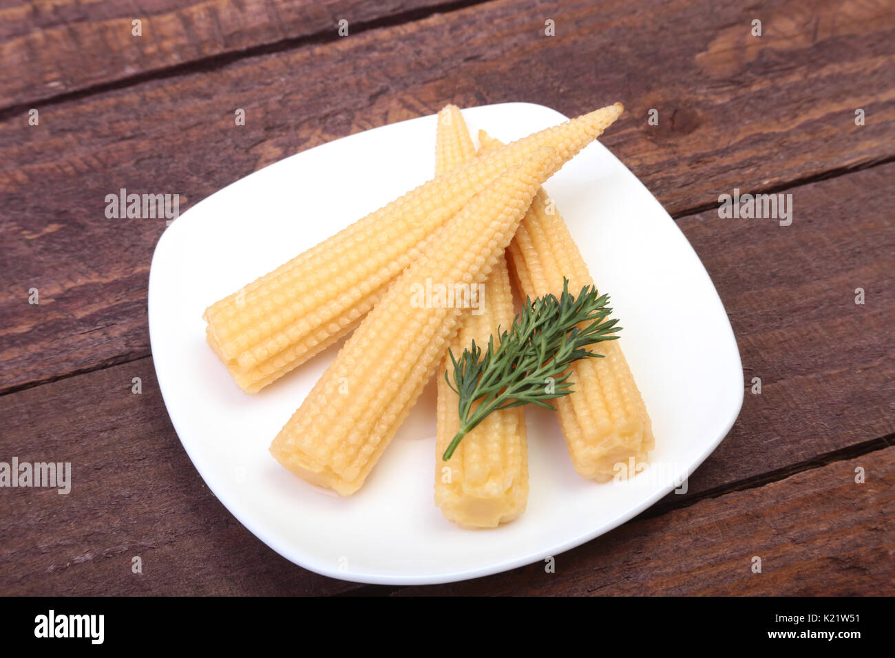 Mini Corn cob preserved on plate on wooden board - Stock Image