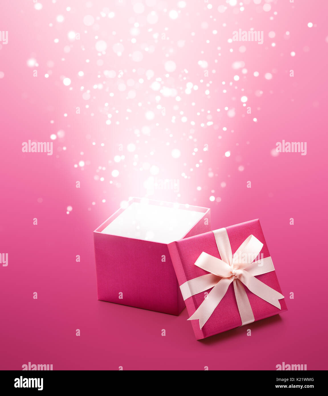 Magical orbs bursting out from pink gift box - Stock Image