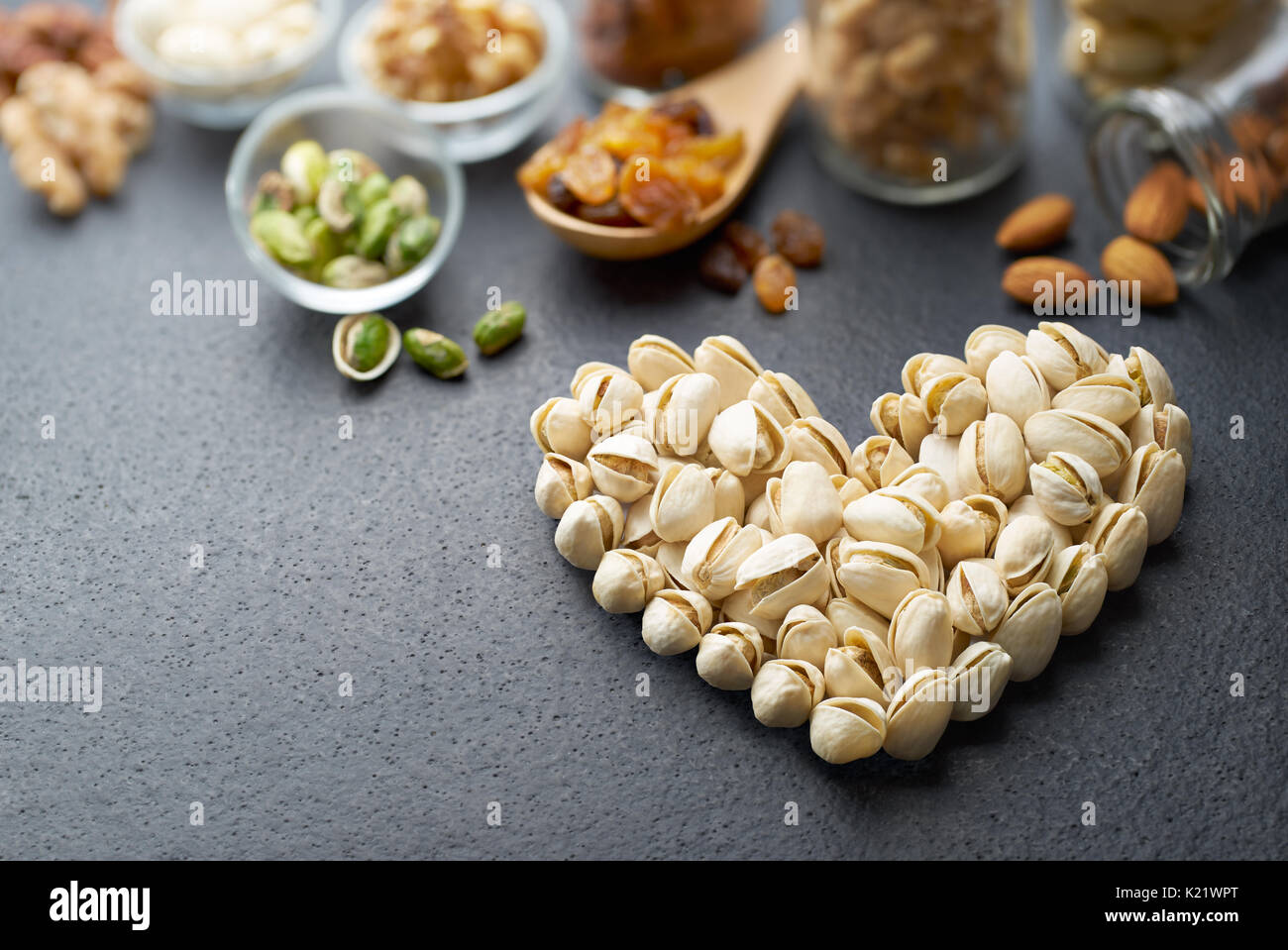 Pistachio nuts forming a heart-shape on slate background - Stock Image