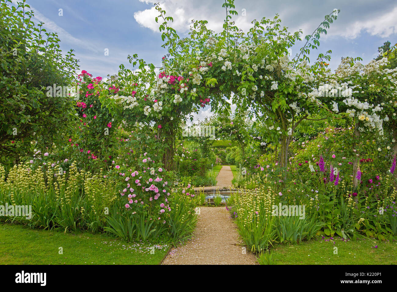 Extensive & stunning English garden with circular pond, herbaceous borders, and pathway leading through archway with climbing roses at Rousham gardens - Stock Image