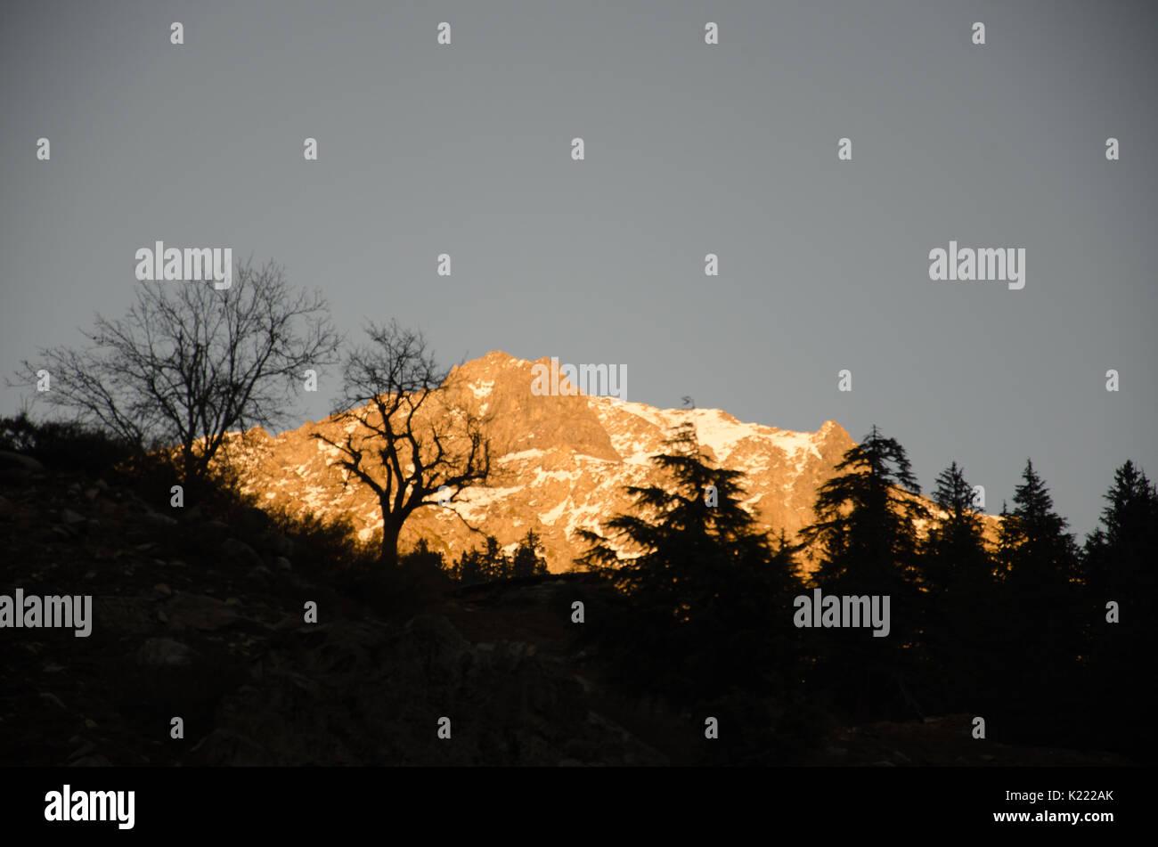Last rays of sun on a mountain. - Stock Image