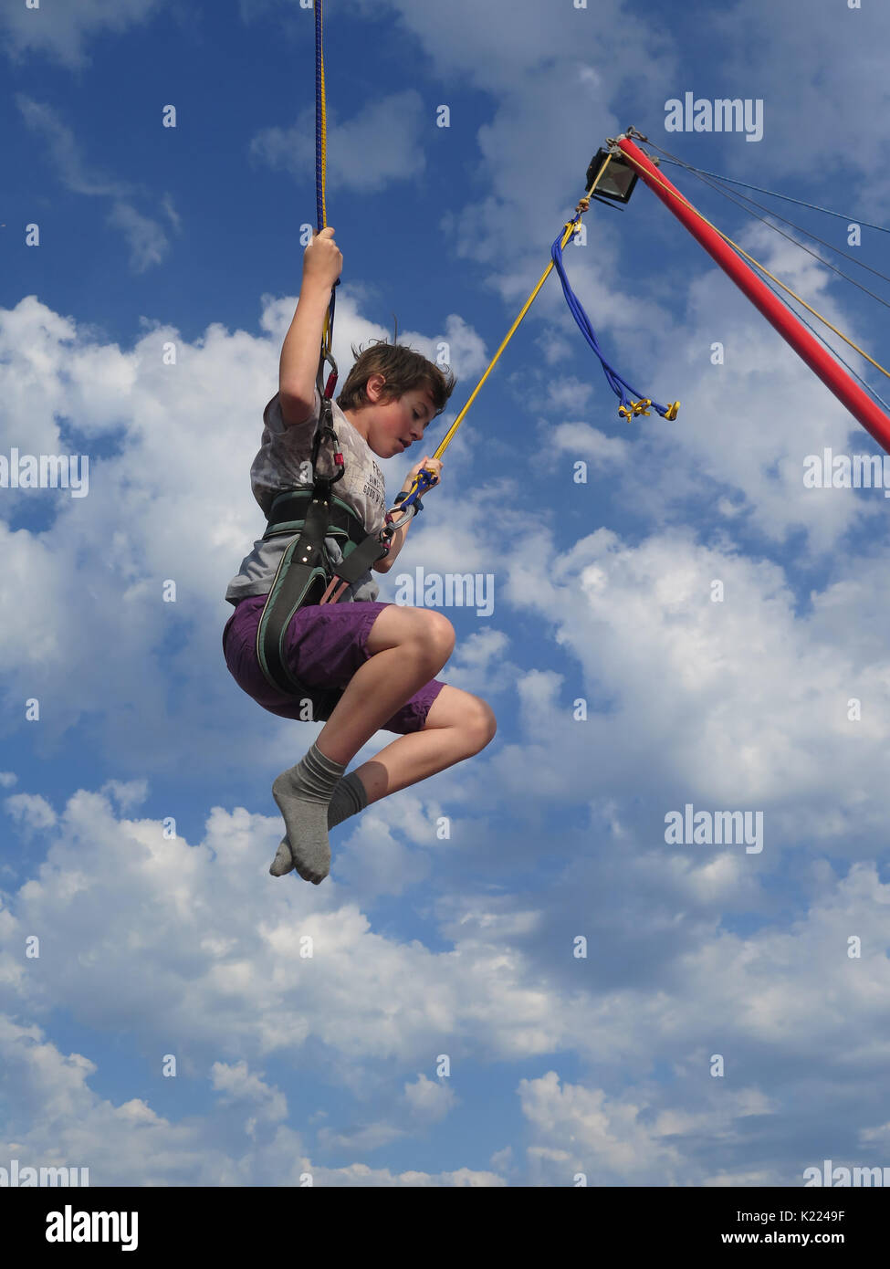 Young Boy Bounces on a trampoline on Bournemouth Pier - Stock Image