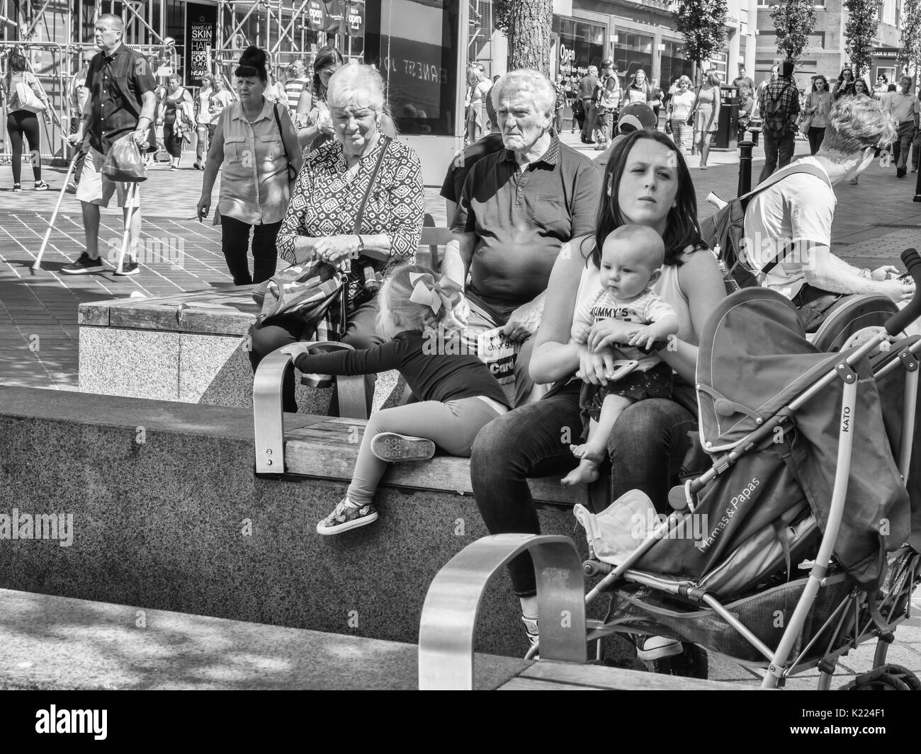 Mother sitting with baby & child watched by elderly woman. Liverpool, England, UK - Stock Image