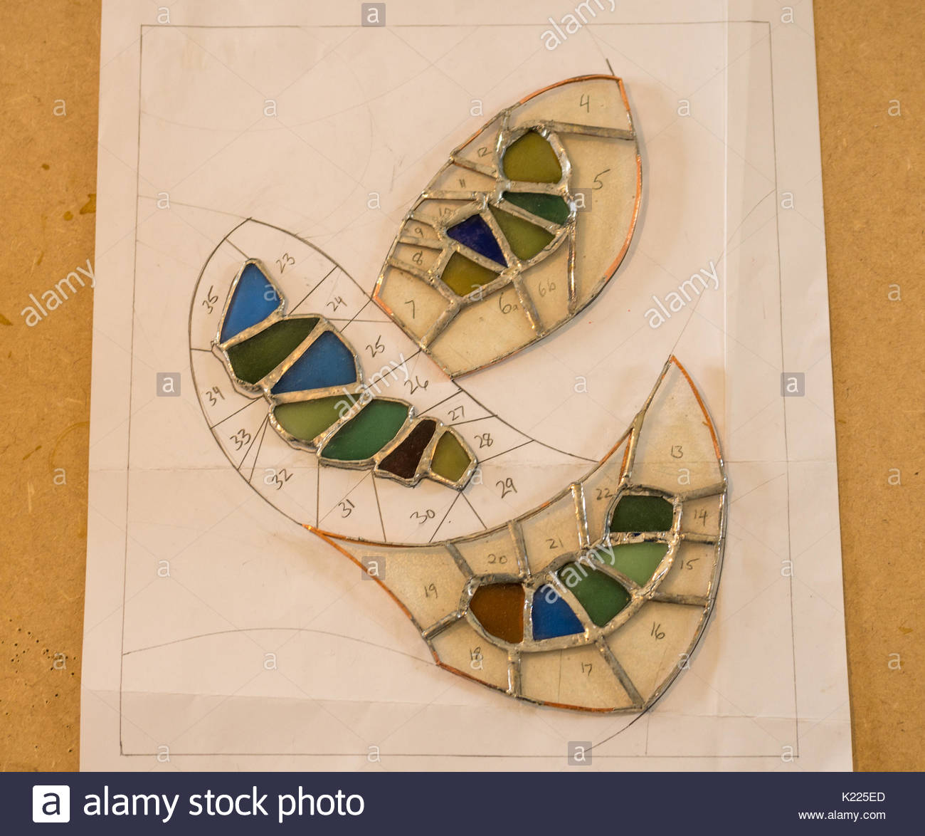 Work in progress with numbered shapes making stained glass and sea glass art work on a work board using copper foil Stock Photo
