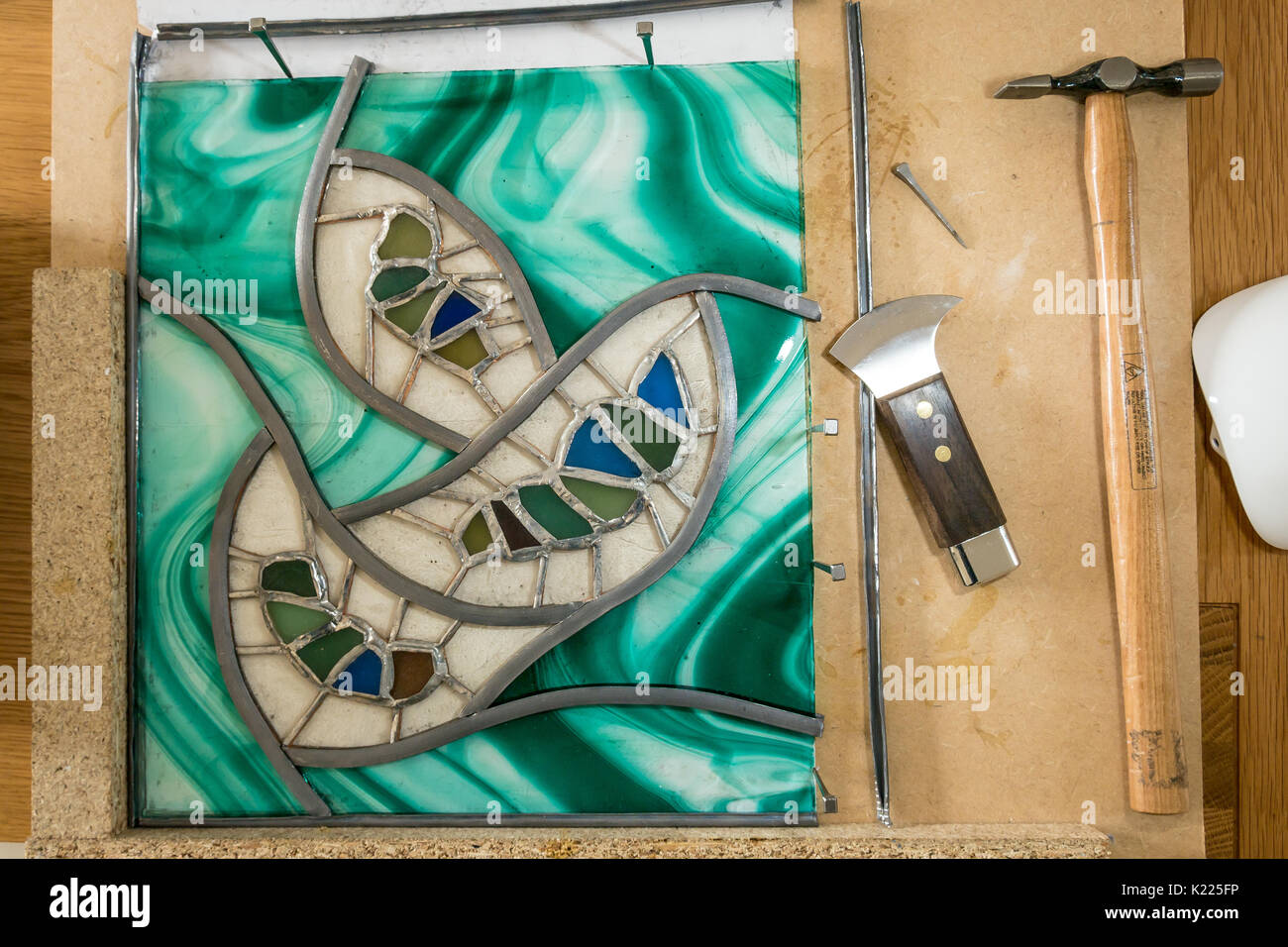 Work in progress making stained glass and sea glass art work using lead came. Work board with lead came, hammer, horseshoe nails and lead knife - Stock Image
