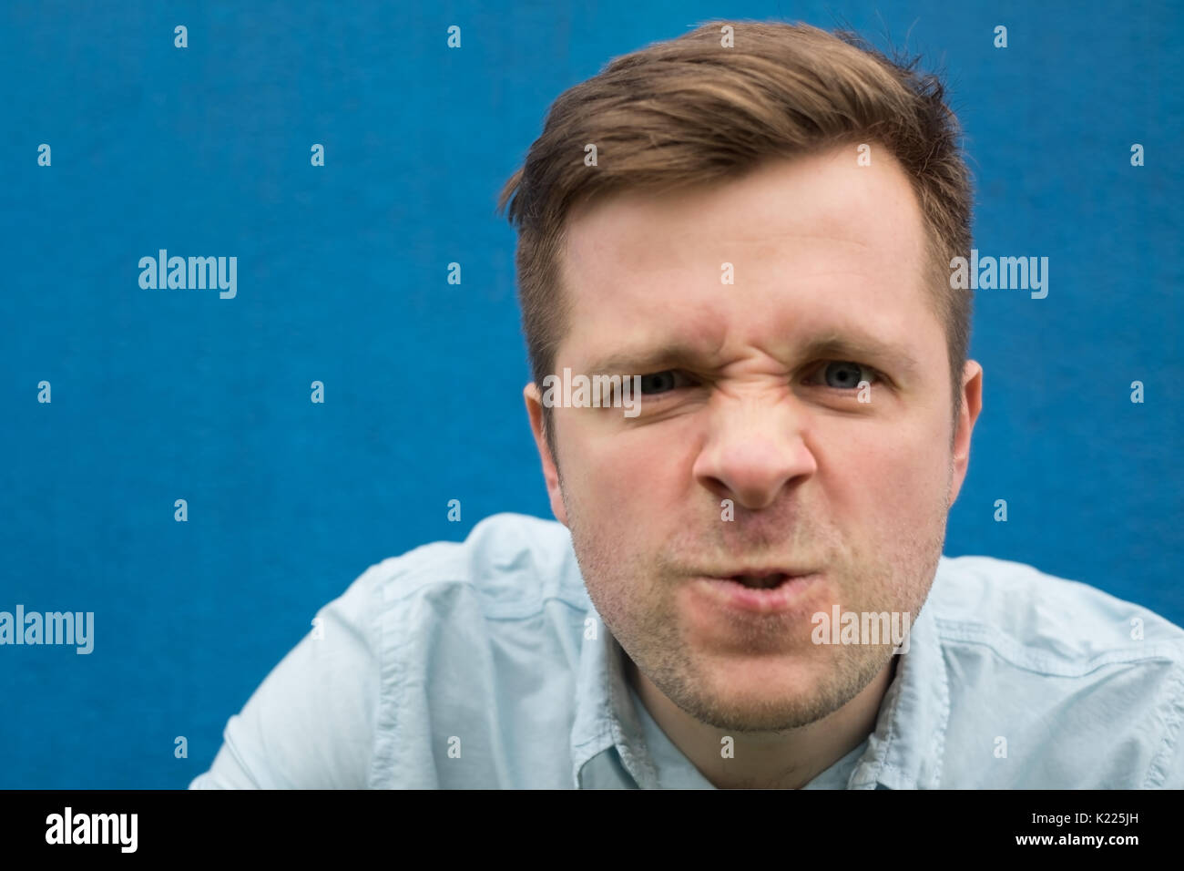 Face of an angry and furious caucasian man on a blue background. - Stock Image