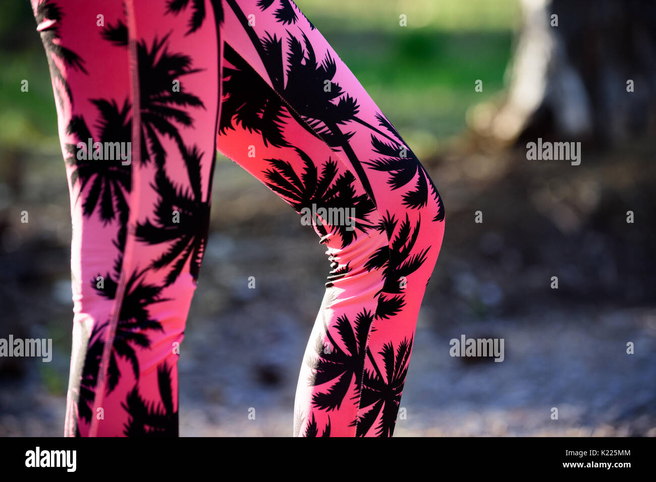 Fit woman in a park during workout, legs detail. Pink palm trees pattern fitness leggings. - Stock Image