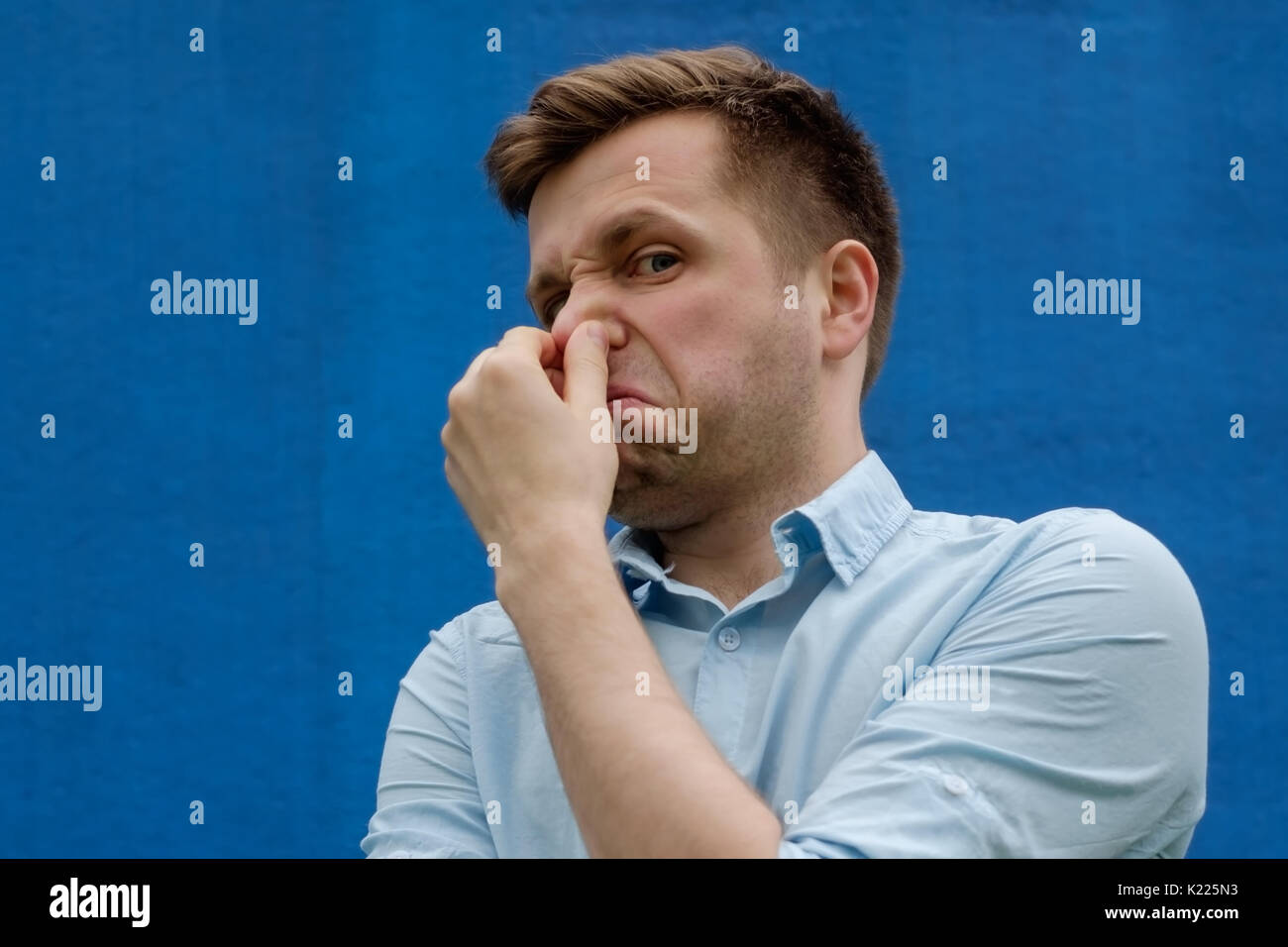 portrait of young caucasian man closing his nose because of terrible smelling - Stock Image