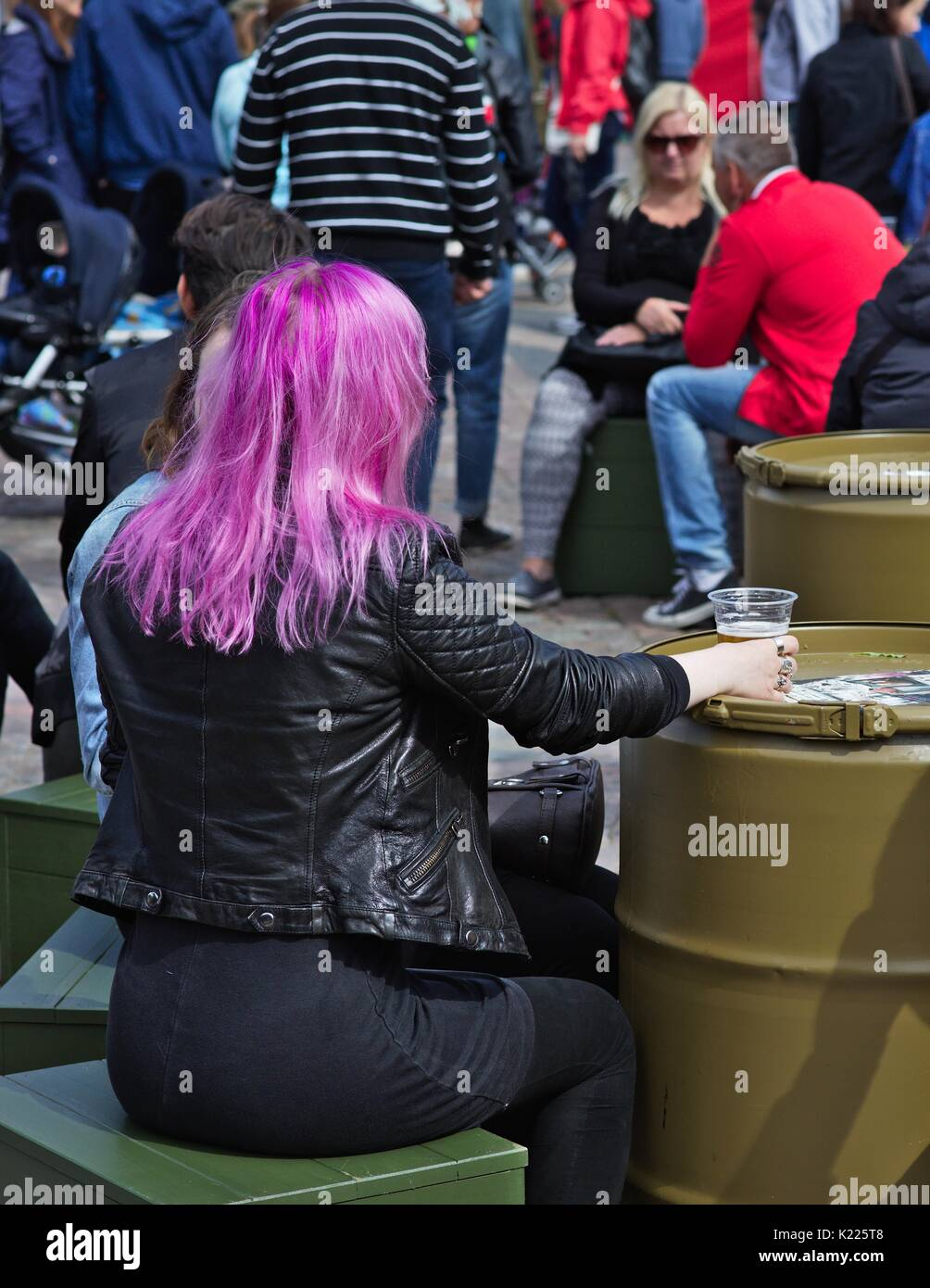 Woman with pink hair, sitting and holding beer glass on barrel table - Stock Image