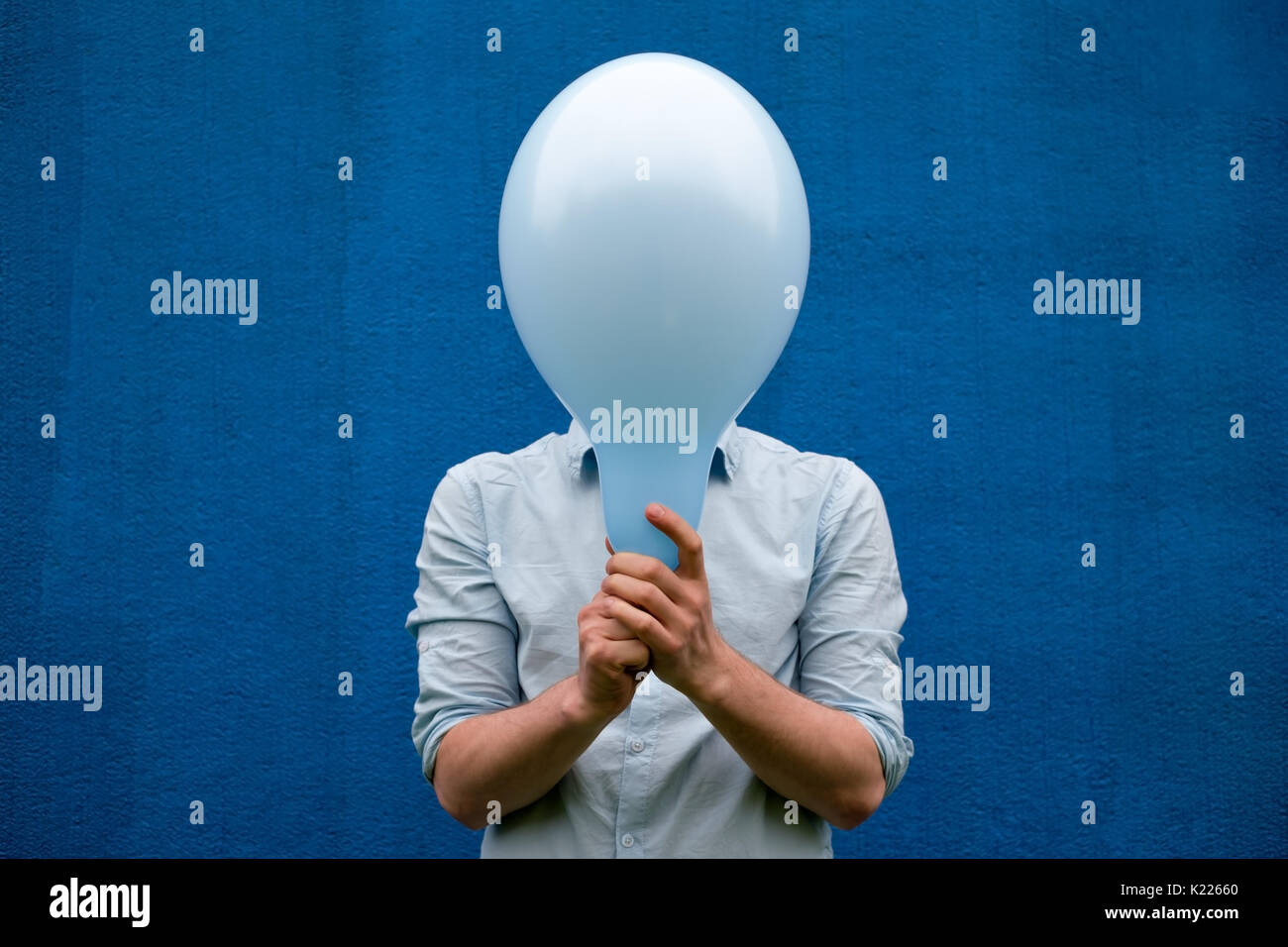 A white man covers his face with a blue balloon. - Stock Image