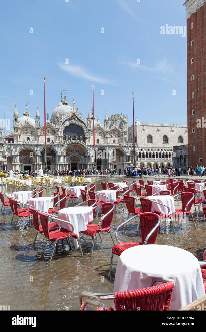 Acqua alta flooding in Piazza San Marco at midday  Venice, italy with water swirling arounf empty restaurant tables Stock Photo