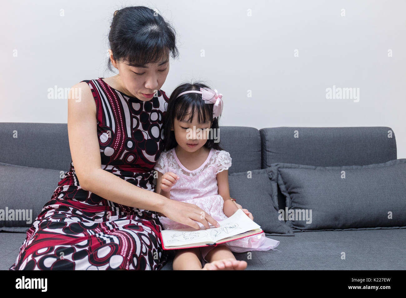 Asian Chinese mother and daughter reading the book on sofa at home - Stock Image