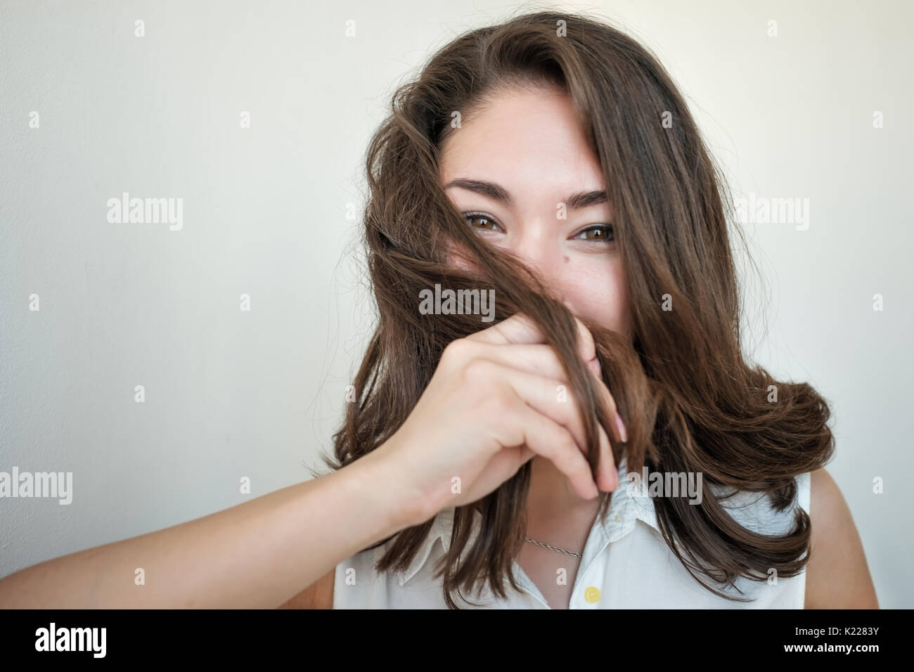 Shy girl hiding her face with hair - Stock Image