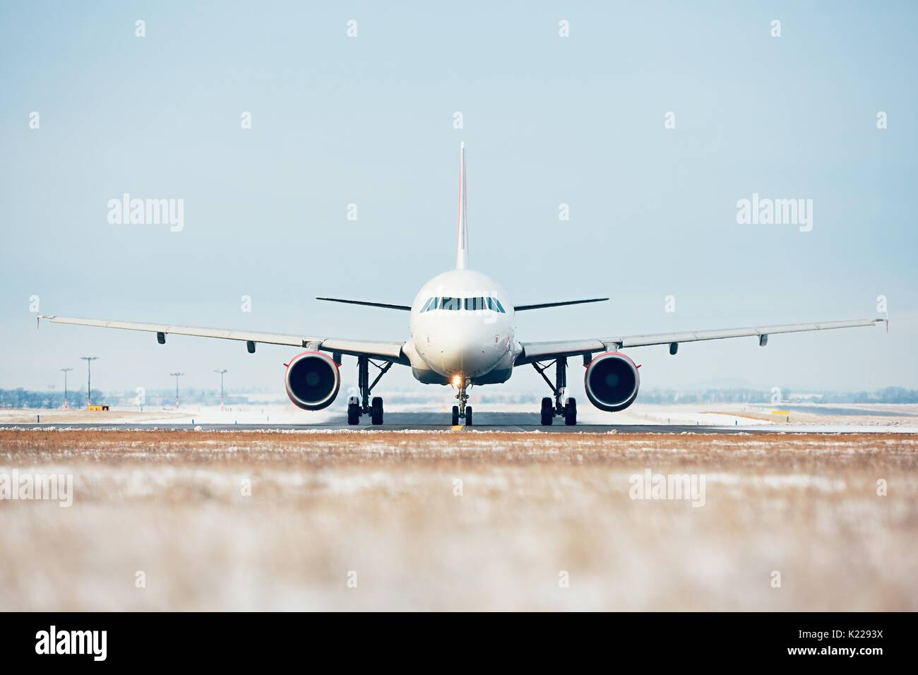 Airport in winter. Airplane taxiing to the runway for take off. - Stock Image