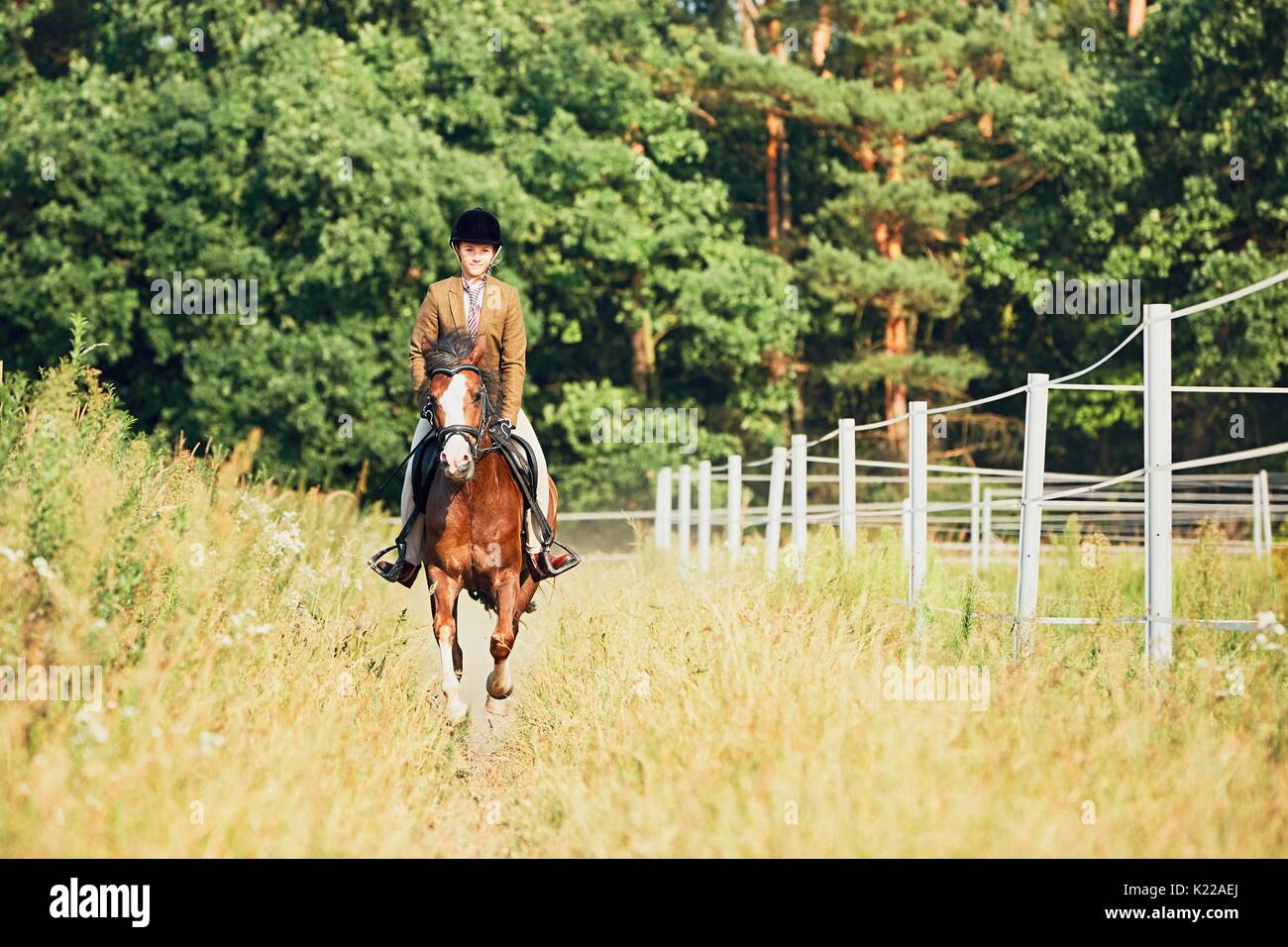 Teenage girl in formal wear riding a horse in nature. - Stock Image