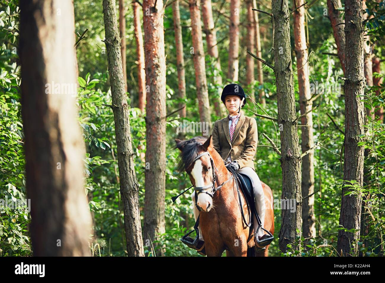 Teenage girl in formal wear riding a horse in forest. - Stock Image