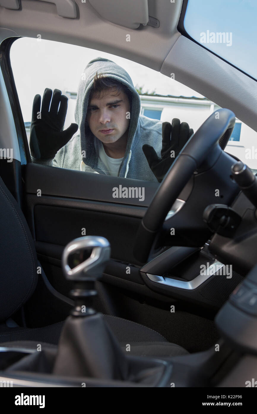 Car Thief Looking Through Window Of Vehicle - Stock Image