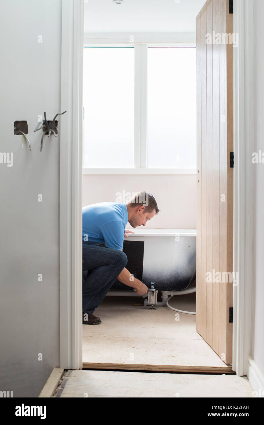 Plumber Installing New Bath Into Bathroom - Stock Image
