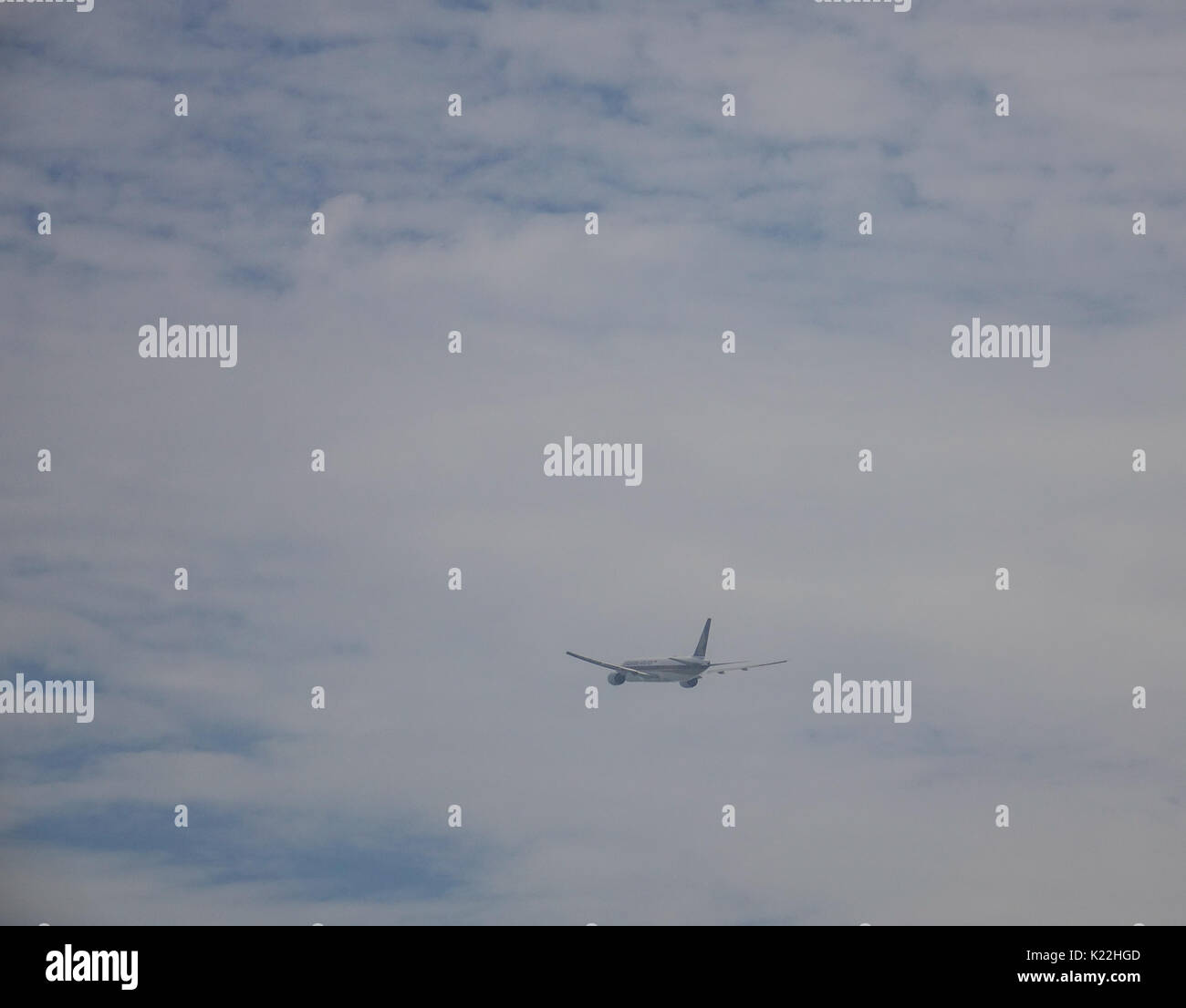 A civil aircraft flying in the sky at misty day in Singapore. - Stock Image