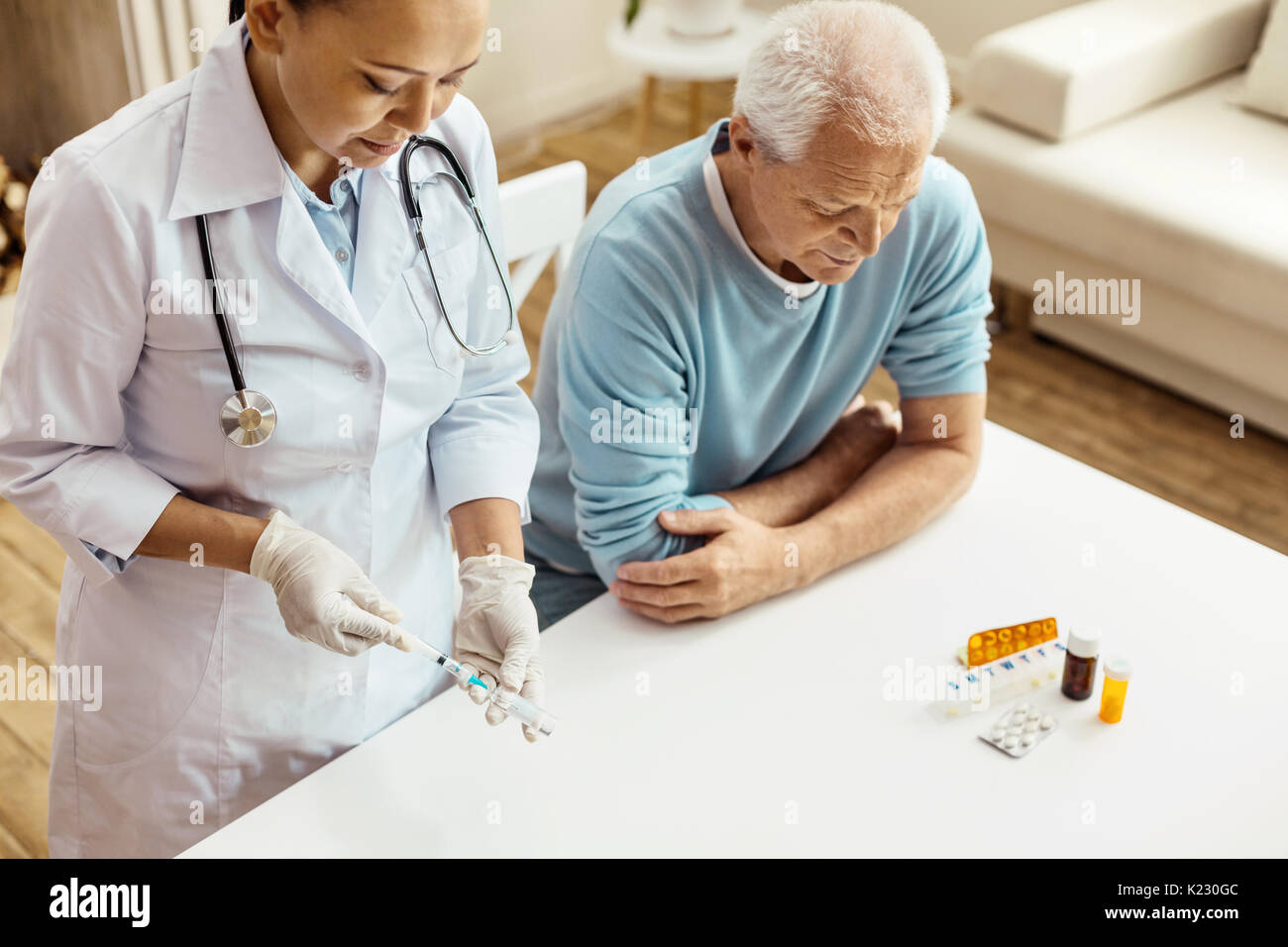 Serious experienced doctor preparing for an injection - Stock Image