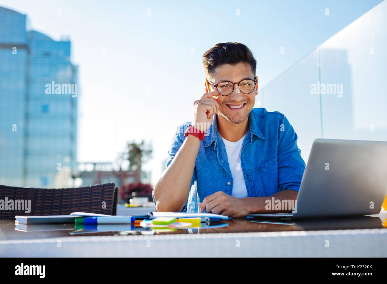 Charming college guy smiling into camera while working on hometask - Stock Image