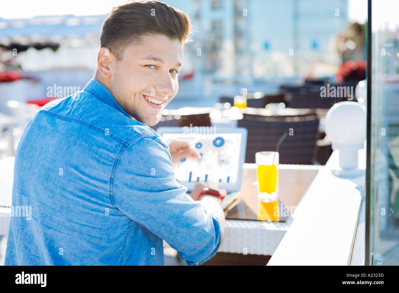 Handsome guy smiling for camera while working outdoors - Stock Image
