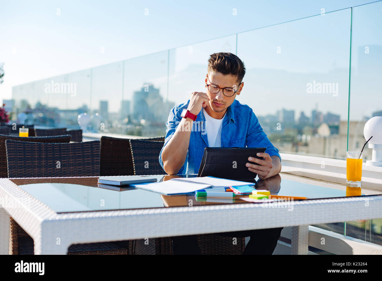Serious college student working on tablet computer - Stock Image