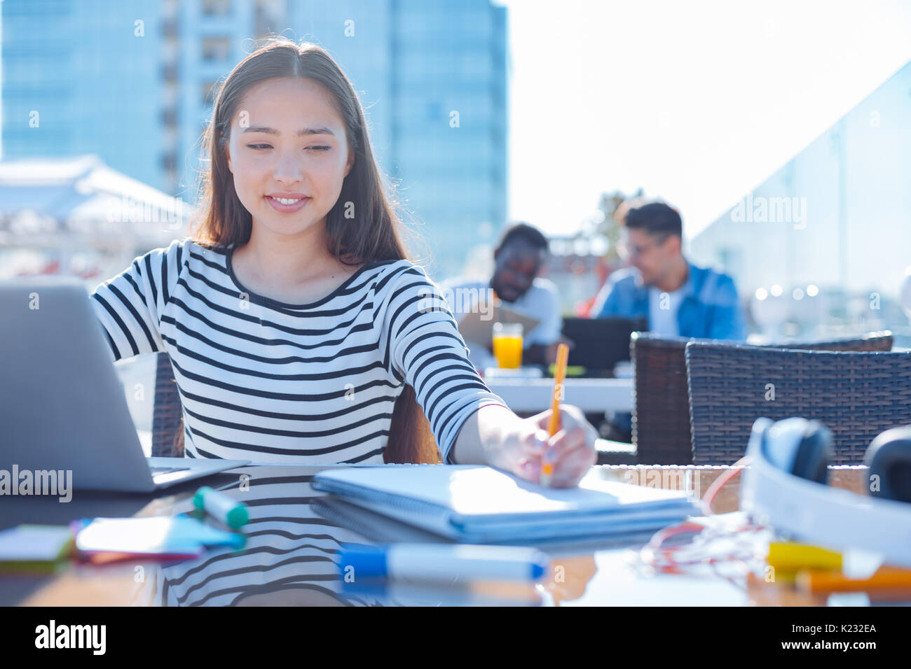 Pretty female student writing down noes - Stock Image