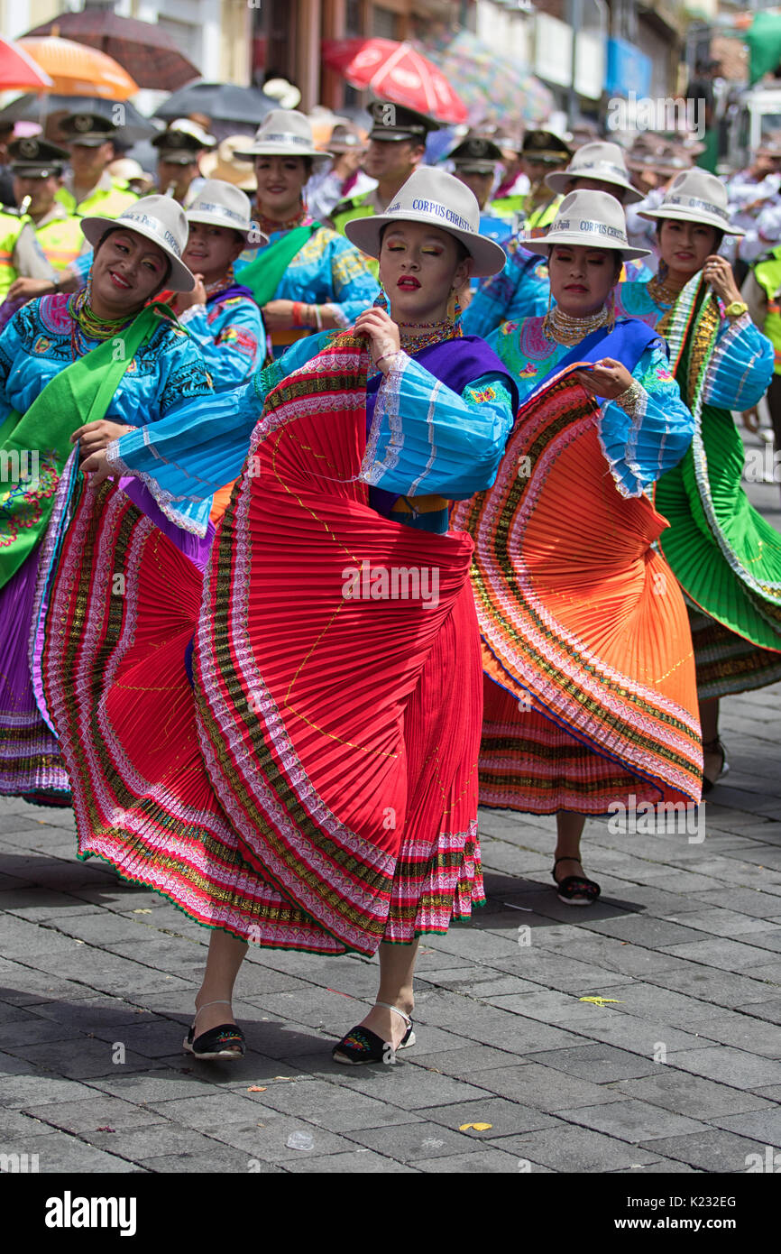June 17, 2017 Pujili, Ecuador: female dancers in bright color traditional wear performing on the street at Corpus Christi celebrations - Stock Image