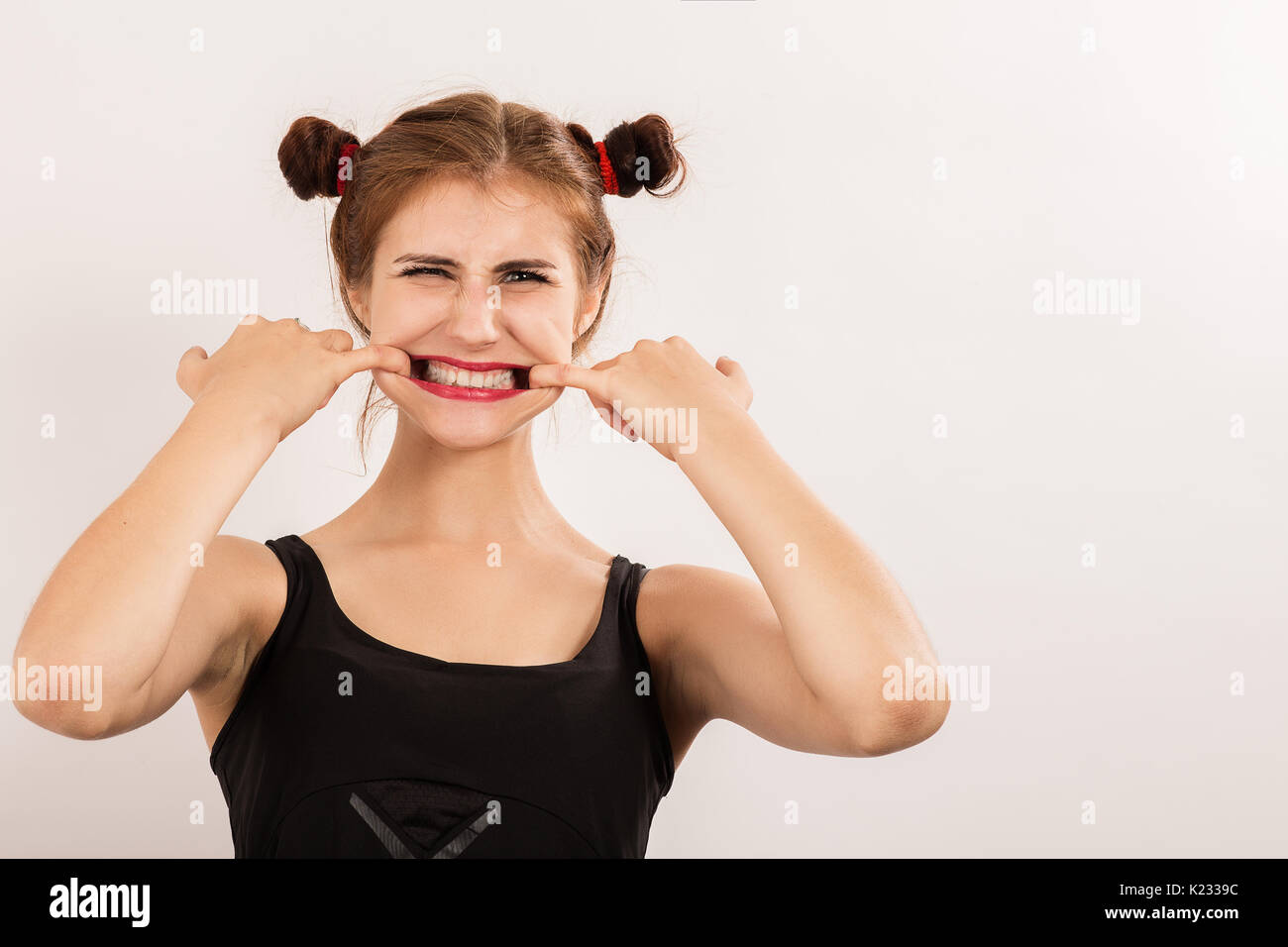 fun beautiful woman grimacing shows her teeth on white background with copy space - Stock Image