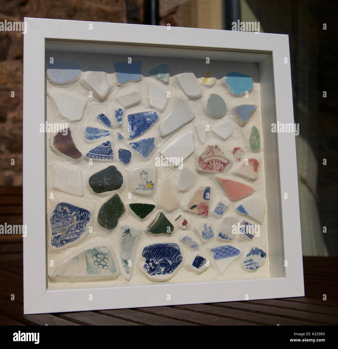 Close up of handmade sea worn pottery mosaic art work set in grout in white frame with blue and white pottery pieces - Stock Image