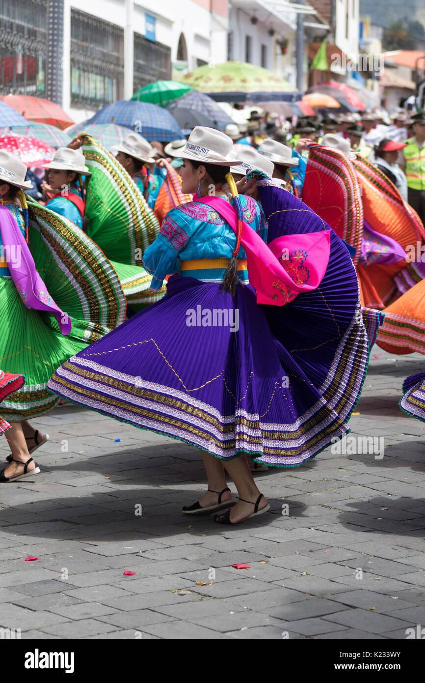 June 17, 2017 Pujili, Ecuador: young female dancers in bright color traditional wear performing on the street at Stock Photo