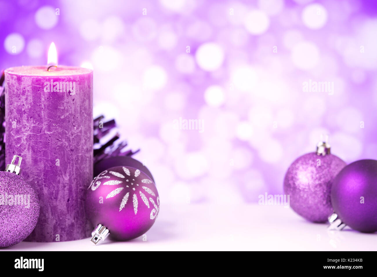 purple and silver christmas baubles and a candle in front of defocused purple and white lights