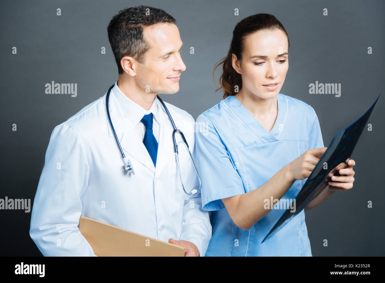 Experienced practitioners chatting over mri scan of patient brain - Stock Image
