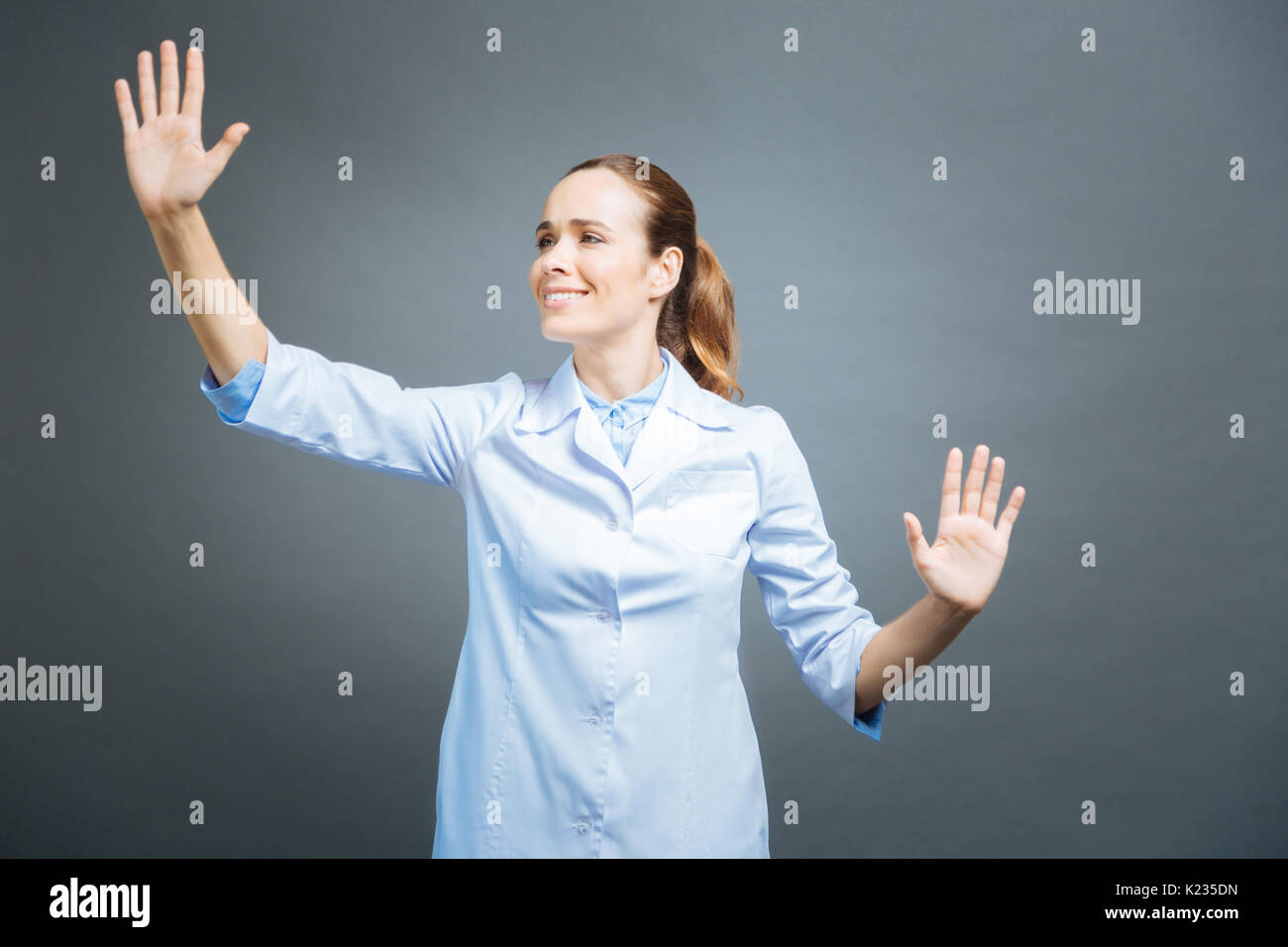 Cheerful medical worker touching invisible touchscreen - Stock Image